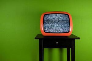 alter orangefarbener Fernseher mit Unterbrechung im grünen Raum foto