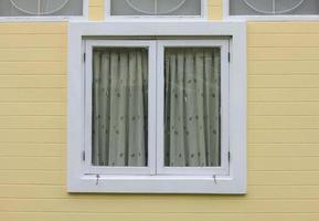 Fenster auf einer gelben Hintergrundwand des Hauses foto