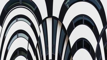 abstrakte Fassadenlinien und Glasreflexion auf modernem Gebäude.