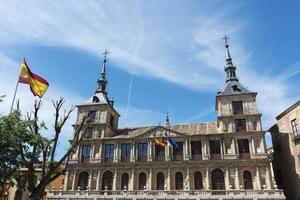 Fassade des Rathauses in Toledo und spanischer Flagge