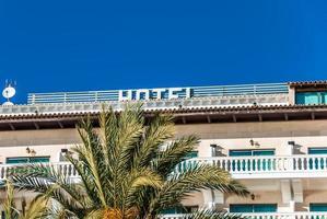 Küstenfassade eines Strandhotels auf Mallorca mit Palme