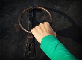 Frauenhand klopft mit Klopfer an die Tür foto