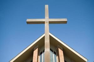 Kreuz vor Kirchendach blauen Himmel