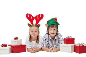 glückliche Kinder mit Elfen- und Rentierhüten, die zwischen Geschenken liegen foto