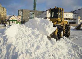 Traktor schaufelt Schnee in Haufen auf der Straße.
