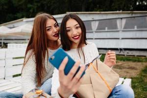 zwei Mädchen machen Selfie mit Geschenken foto