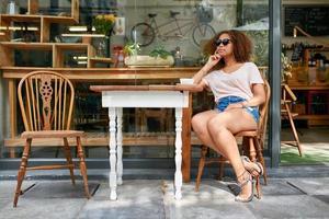 junge afrikanische Frau, die am Kaffeehaus sitzt foto