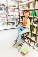 Mädchen mit zwei Zöpfen und Tablette sitzt auf der Leiter