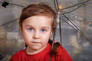 Porträt des kleinen süßen Mädchens mit einem Regenschirm foto