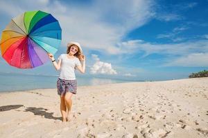 fröhliches junges Mädchen mit Regenbogenschirm, der Spaß auf dem hat