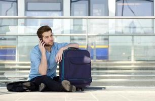 männlicher Reisender, der auf Boden sitzt und auf Handy spricht foto