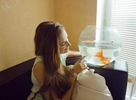 hübsche Frau, die mit Goldfisch zu Hause spielt, Sonnenlichtmorgen foto