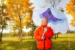 Junge mit blauem Regenschirm steht unter strömendem Regen foto