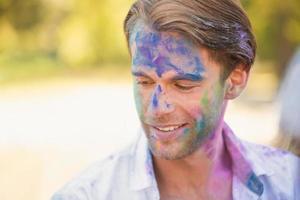 junger Mann, der Spaß mit Pulverfarbe hat foto