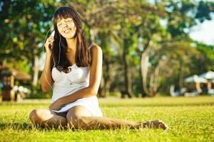 Frau sitzt auf dem Rasen und hört Musik foto