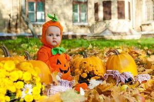 Kind im Kürbisanzug auf Hintergrund des Herbstlaubs