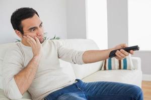 gutaussehender Mann, der sich von Fernsehprogrammen langweilt foto