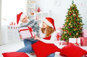glückliches Familienpaar mit einem Geschenk an Weihnachten zu Hause