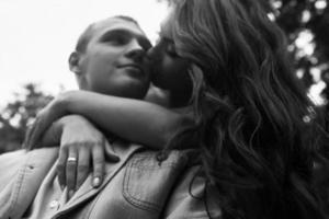 junges europäisches Paar, das auf einer Parkbank kuschelt