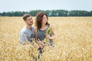 Mädchen und Mann im Feld mit Weizen. foto