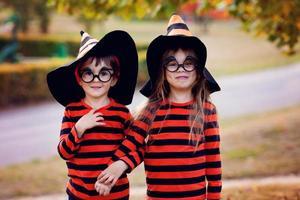 Junge und Mädchen im Park in Halloween-Kostümen foto