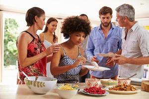 Freunde, die sich Essen servieren und auf einer Dinnerparty reden foto
