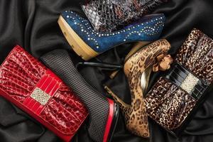 Drei Schuhe und Geldbörsen sind auf der schwarzen Seide