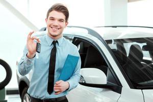 lächelnder junger Mann, der Autoschlüssel hochhält, neben einem neuen Auto foto
