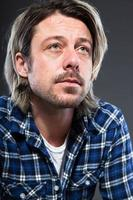 ausdrucksstarker junger Mann mit blonden langen Haaren und Bart.