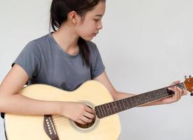 hübsches Mädchen, das Gitarre übt. foto
