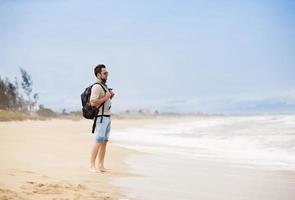 Mann geht am Strand spazieren foto