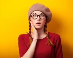rothaariges Mädchen mit Zöpfen auf gelbem Hintergrund.