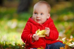 fröhliches Baby in einem roten Kleid, das mit gelben Blättern spielt foto