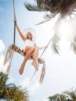 Unteransicht einer Frau, die auf der Baumschaukel schwingt foto
