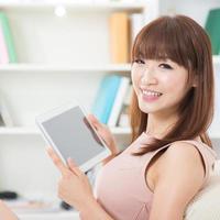asiatisches Mädchen mit Touchscreen-Tablet foto