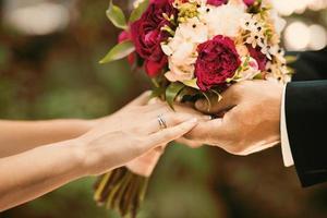 frisch verheiratetes Paar, das am Hochzeitstag Hände hält. foto