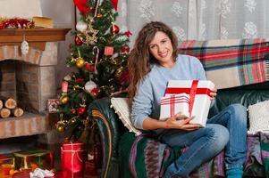 Frau sitzt auf der Couch und hält Weihnachtsgeschenk foto