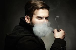 künstlerisches dunkles Porträt des jungen schönen Mannes foto