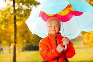 glücklicher Junge mit blauem Regenschirm, der unter Regen steht foto