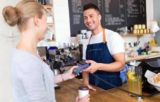 Frau, die für Kaffee bezahlt foto