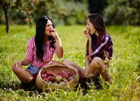 schöne Frauen, die einen Apfel beißen foto