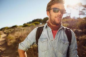 glücklicher junger Mann, der in der Landschaft wandert foto