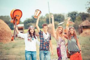 Hippie-Gruppe spielt Musik und tanzt draußen foto