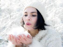schönes Winterporträt der jungen Frau in der verschneiten Landschaft