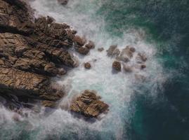 Langzeitbelichtung von Wellen, die auf Felsen spritzen foto