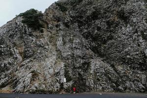 Person, die Foto des grauen felsigen Berges macht