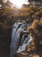Wasserfall zwischen Felsen und Bäumen foto