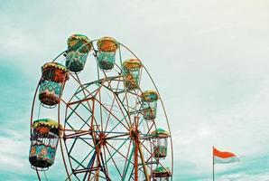 Riesenrad und Flagge gegen bewölkten blauen Himmel foto