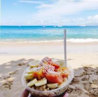 Person, die einen gelben und orange Obstsalat in einer Tasse am Strand hält foto