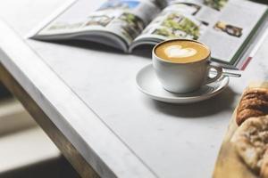 weiße keramische Kaffeetasse mit Untertasse auf weißem Tisch foto